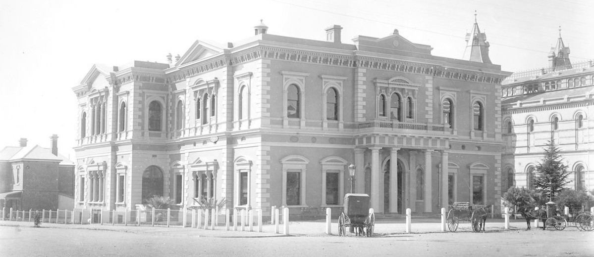Image: A large, two-storey building fronted by a dirt street and two horse-drawn carts