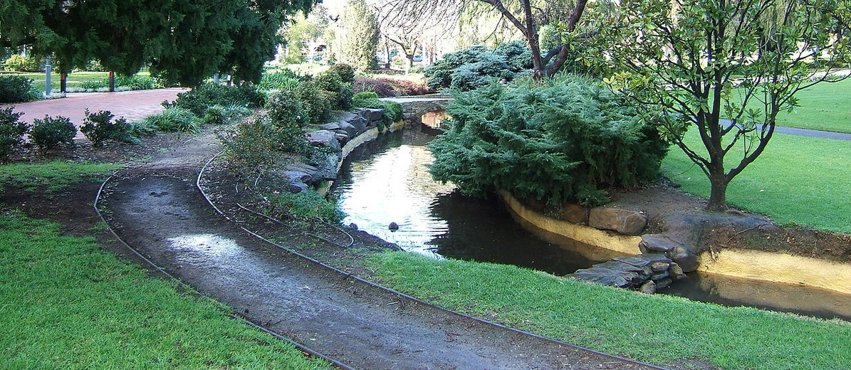 Image: A creek winds through a landscaped wooded parkland. A footpath follows the course of the creek