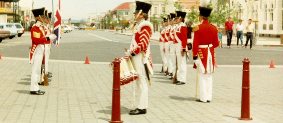A group of men wearing red soldiers uniforms stand in two lines facing in front of a wide street extending into distance