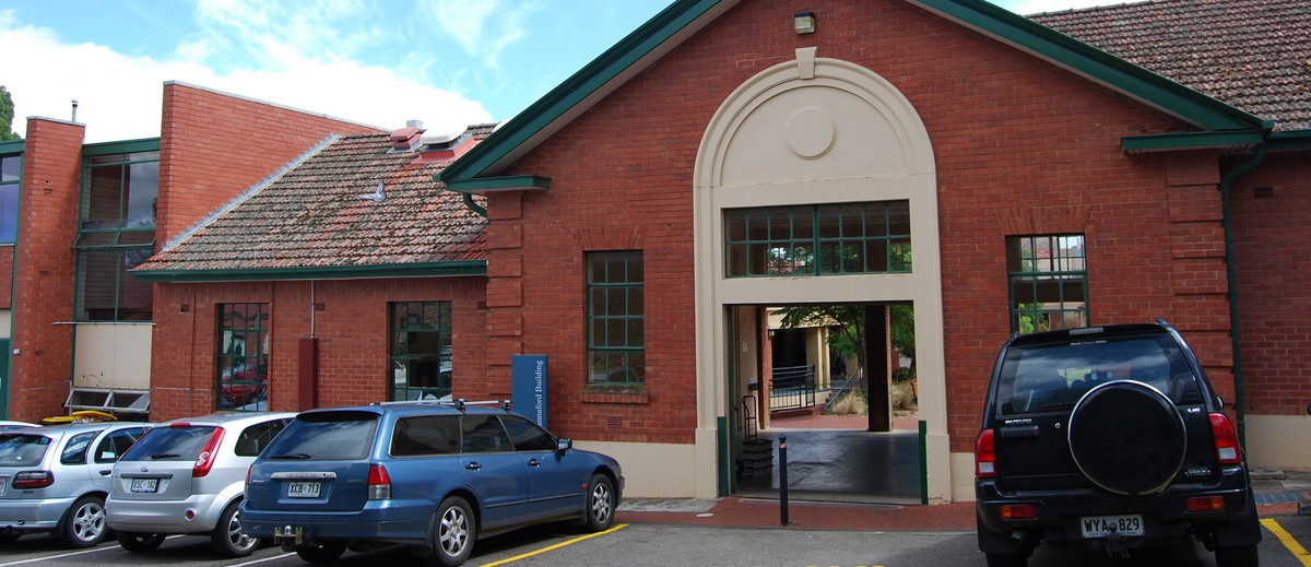 Image: The front of a single-storey brick building with a white arch entranceway. Several modern auto-mobiles are parked in front of the building