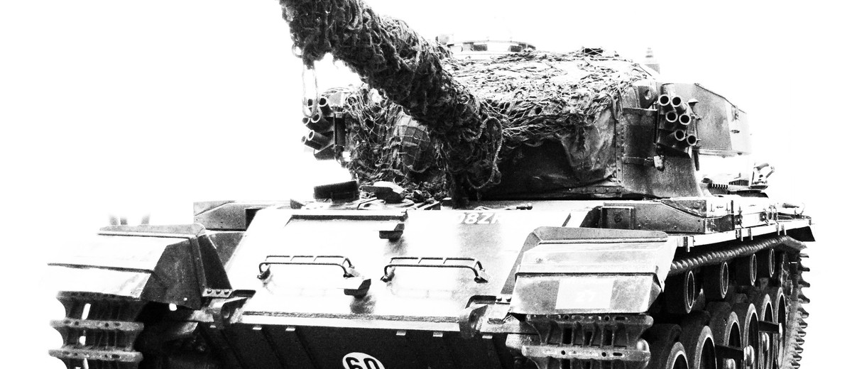 Image: Photograph of the front of an armoured tank. The gun is slightly elevated and the number '60' is painted on the front underside of the tank