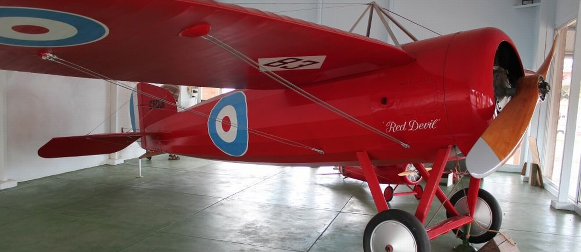 Image: A bright red First World War-era monoplane on static exhibit in a museum