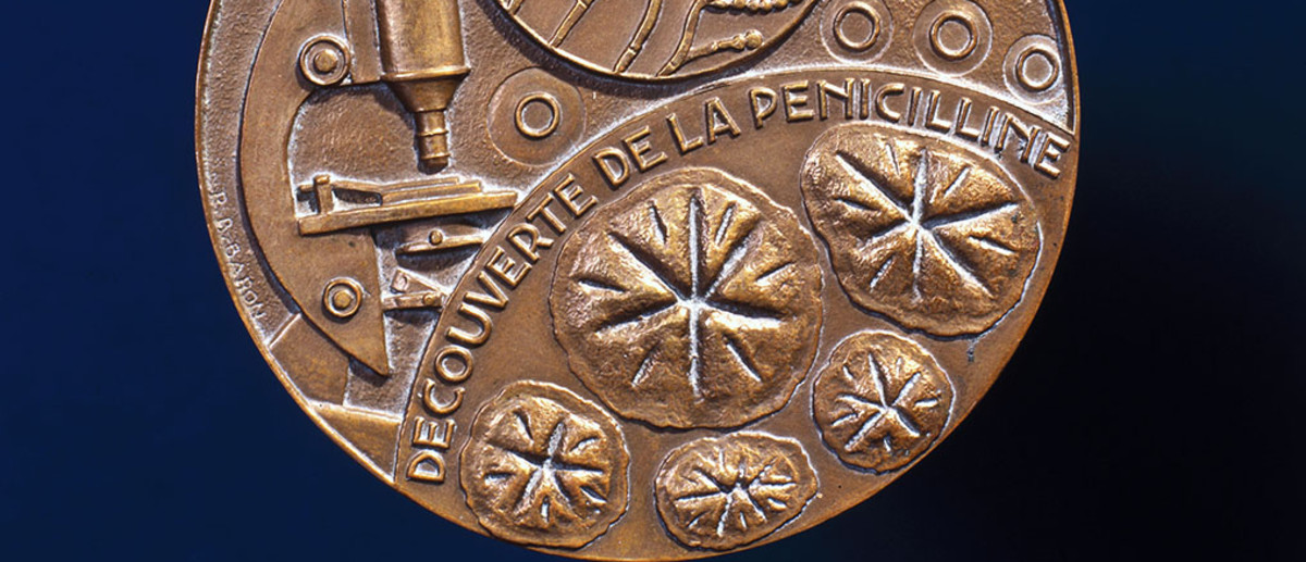 Image: An ornate bronze medal with the words 'Decouverte de la Penicilline' embossed on it. Other scientific motifs, including a microscope and a penicillin bacterium, are also featured on the medal