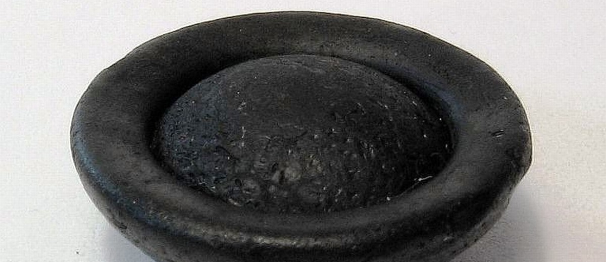 Image: A black button-shaped object made of natural glass. It is roughly circular, and features a convex face. The opposite face comprises a shallow depression with a central convex surface emerging from it
