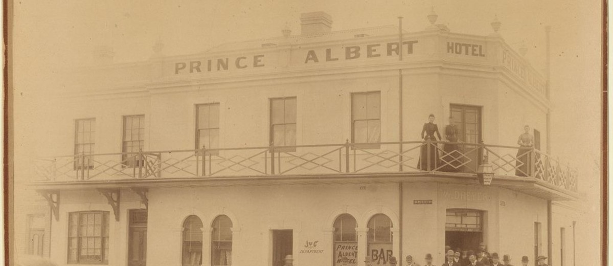 Image: group of people standing below and on balcony of large stone building