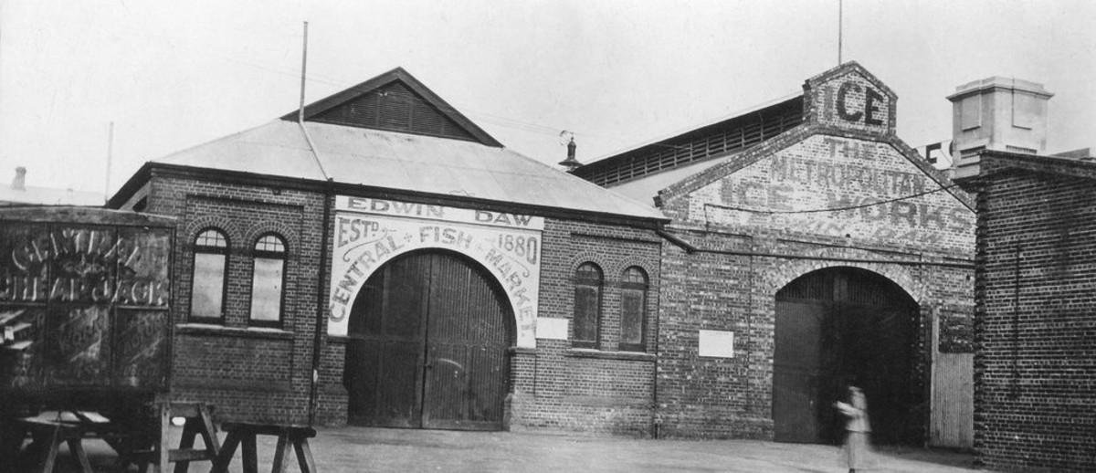 Image: A woman walks by two long brick buildings, one of which has the words 'Edwin Daw Central Fish Market' on its facade