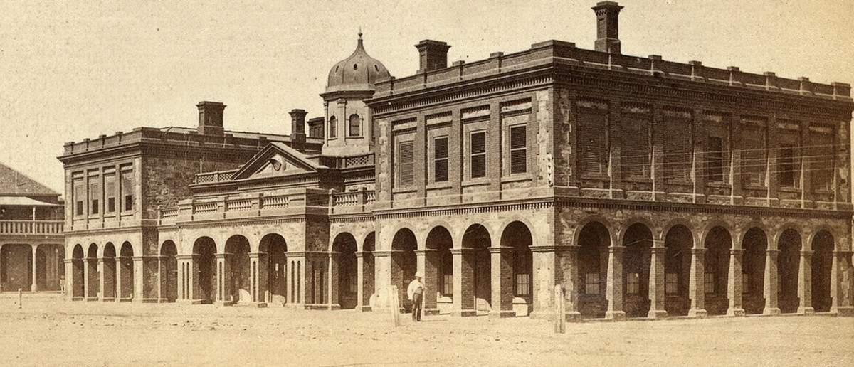 Image: A large, two-storey stone building in Victorian Italianate style. It features open archways on the ground floor, and its central section is topped by a cupola