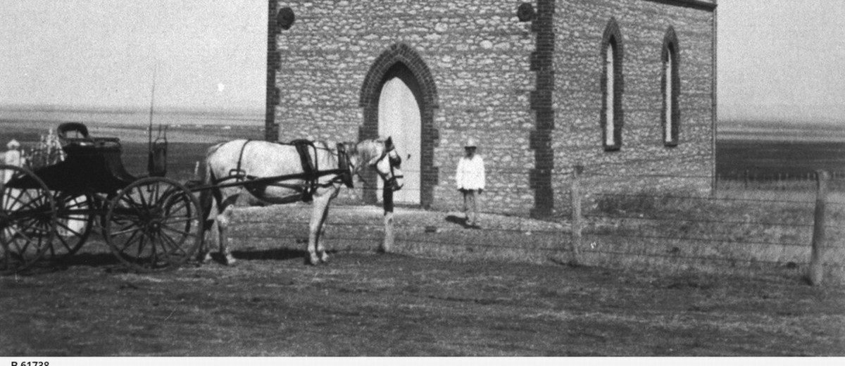 Image: A Caucasian man in a hat and light-coloured top stands outside the front door of a small Bluestone chapel in a remote setting. A horse and buggy stand nearby