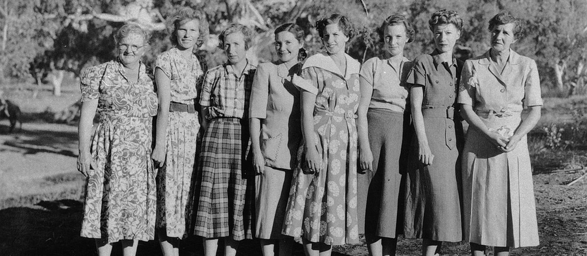 Image: A group of young Caucasian women flanked by two middle-aged Caucasian women pose for a photograph in rural central Australia. All of the women are wearing dresses of 1940s and 1950s vintage