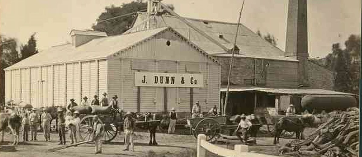 Image: men and horse drawn carts in front of flour mill with J Dunn and Co sign