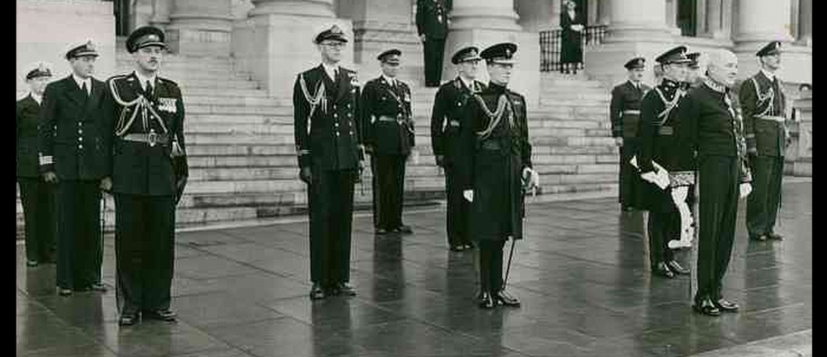 Image: A middle-aged man attired in a ceremonial dress uniform stands at the head of a group of military officers, all of whom are similarly attired. A large building with columns is visible in the immediate background
