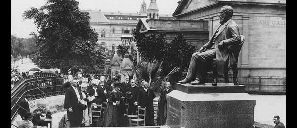Image: A crowd of people in Edwardian-era attire gather around a large bronze statue of a bearded man sitting in a chair