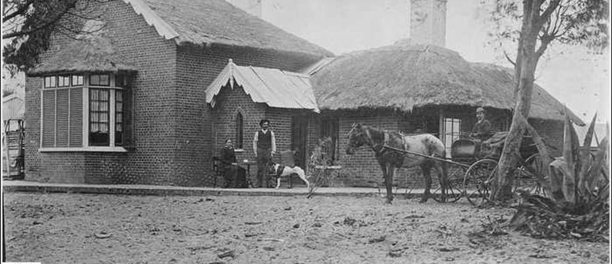 Image: man stands with dog in front of a brick house with a thatched roof. Beside him sits a woman while another man drives a horse drawn buggy.