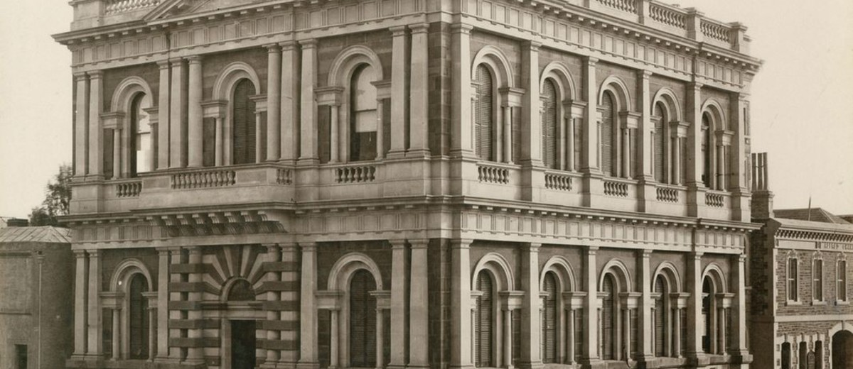 Image: Black and white photograph of a two storied stone building featuring arched windows