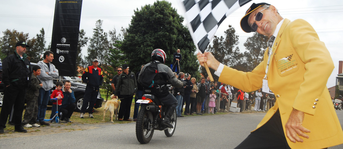 Image: man waving checkered flag as motorbike rides away