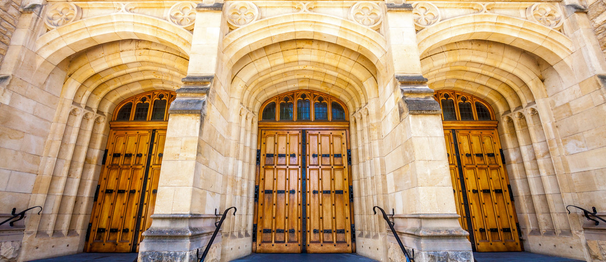 Image: The entrance to an ornate, historic building made of stone. Three large wooden doors are contained within corresponding stone archways