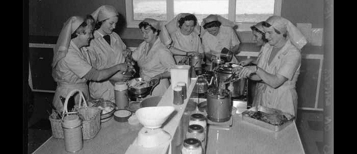 Image: A group of seven Caucasian women in 1960s attire that resemble nursing uniforms prepare and pack food in a small kitchen