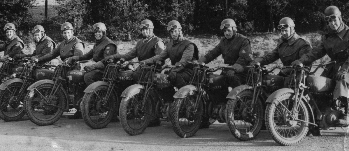 Image: Nine men wearing Second World War-era military uniforms each sits astride a motorcycle. Each man is wearing a helmet with goggles, and all are arranged in a line abreast of one another