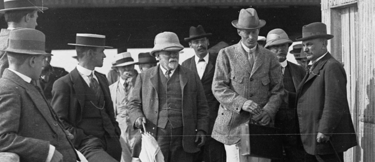 Image: A man in a hat and suit walks on a jetty ahead of a group of other men. The side of a corrugated metal building is visible to the right of the men