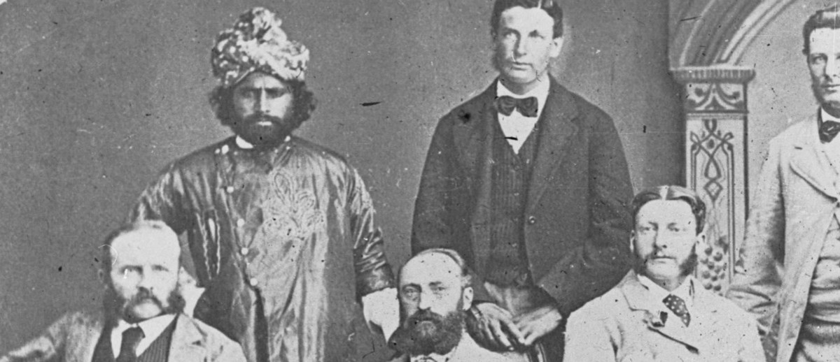 Image: A group of seven men, including an Afghan cameleer and Aboriginal tracker, pose for a photograph. The cameleer is dressed in ornate traditional costume with a turban