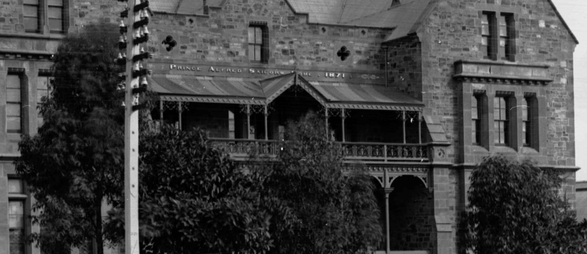 Image: A large, three-storey mid-nineteenth century bluestone building fronted by a dirt street. A sign reading 'Prince Alfred Sailors' Home, 1871' is visible above the front entrance