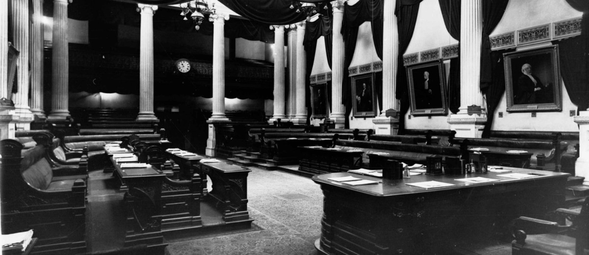Image: wooden desks and leather bench seats are arranged around a room which is lined with white columns and decorated with portraits and swathes of dark fabric.
