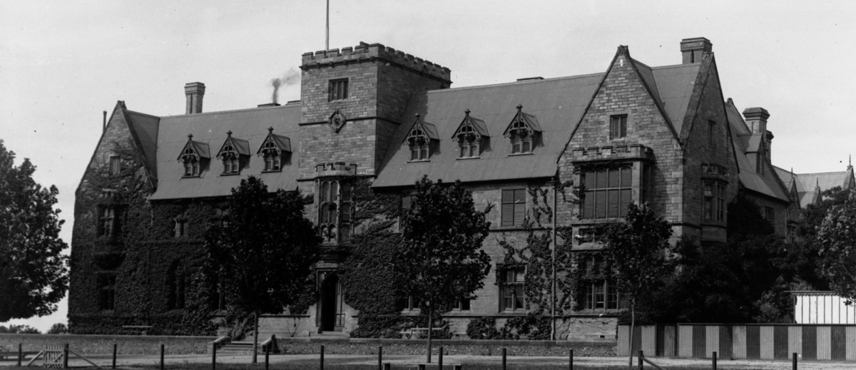 Image: A large, two-storey stone building with a central, square tower and steep, peaked roof
