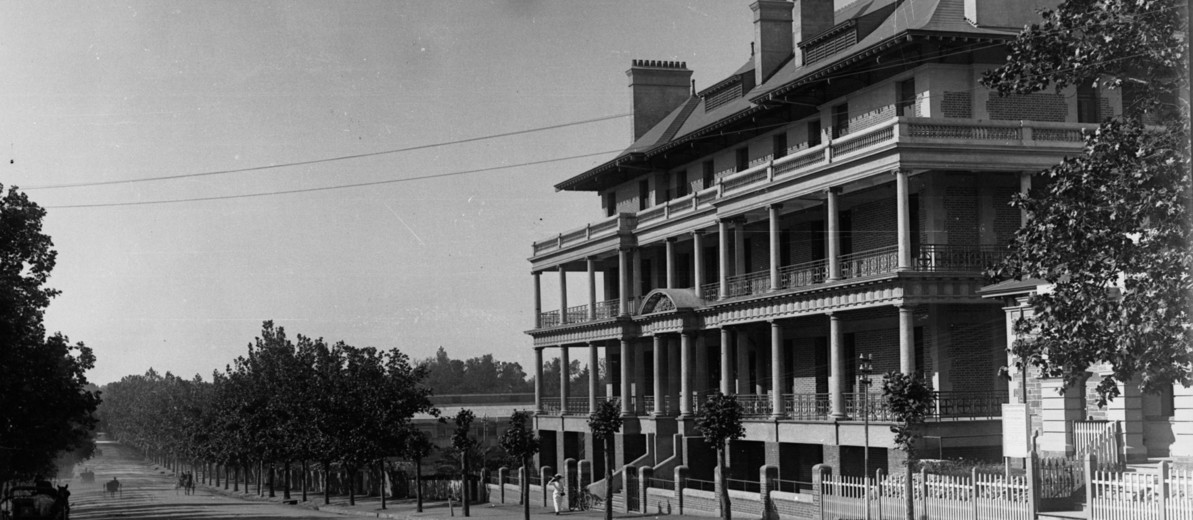 Image: A large, four-storey brick building sits alongside a dirt road lined with trees. Four horse-drawn carts are visible travelling along the street