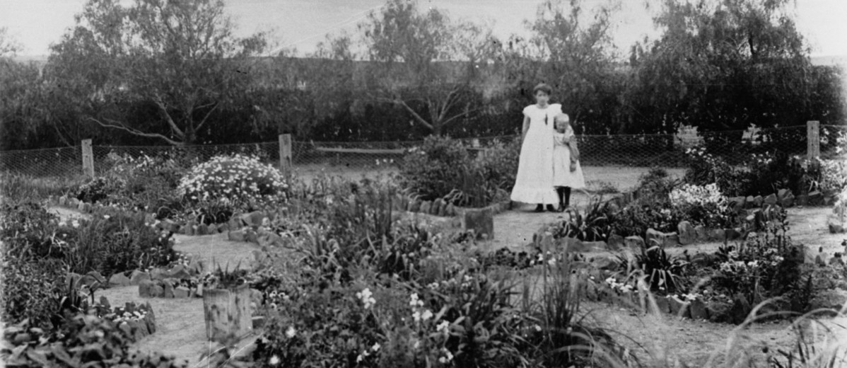 Image: Two young women stand in a large garden with a variety of flowering and other plants
