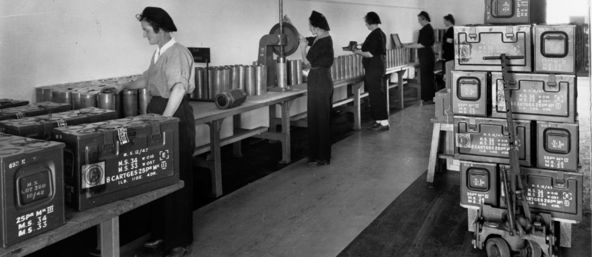 Image: A group of women stand at a long table manufacture and pack large-calibre artillery shells