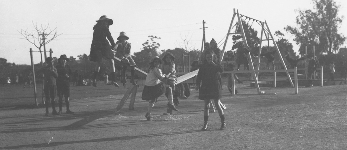 Image: A group of girls and boys play on playground equipment, including see-saws and swings