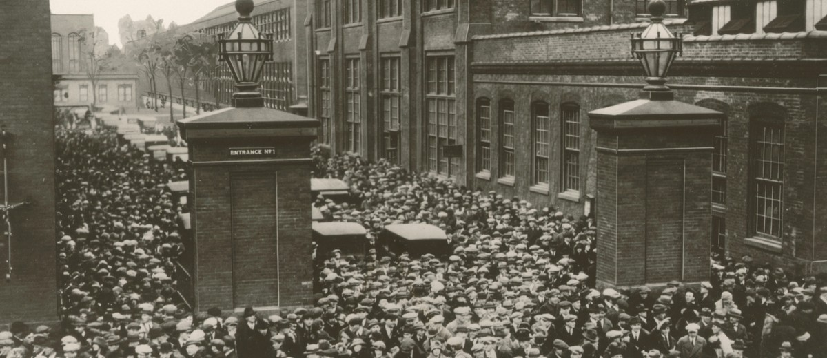 Image: A mass of men and women in 1920s attire walk through the entrance gates of a large, multi-storey brick factory