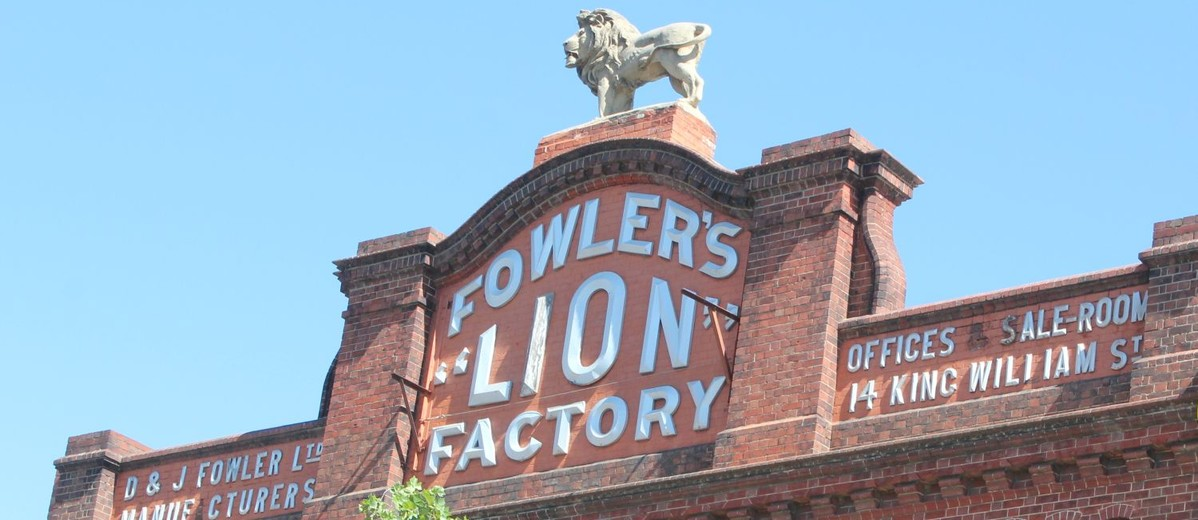Image: Lion sculpture on top of red brick parapet baring signage 'Fowler's Lion Factory'