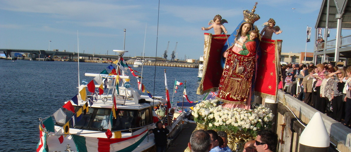 Image: A group of people watch men in Catholic vestments carry an effigy of the Madonna and Child to a motorboat moored at a wharf