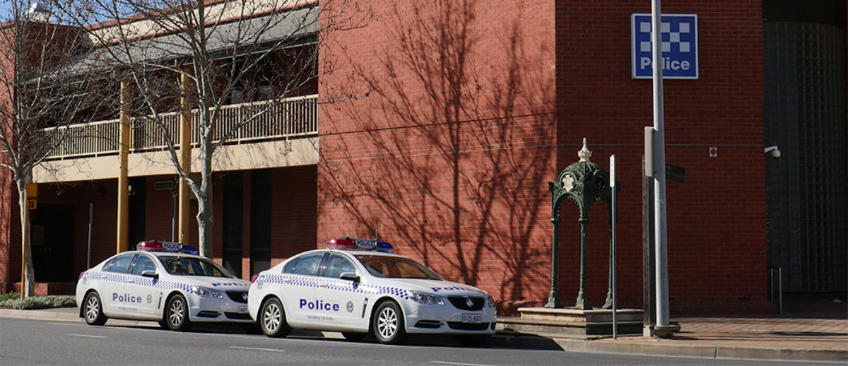 Image: Large red brick building on street corner with fountain and two police cars in front