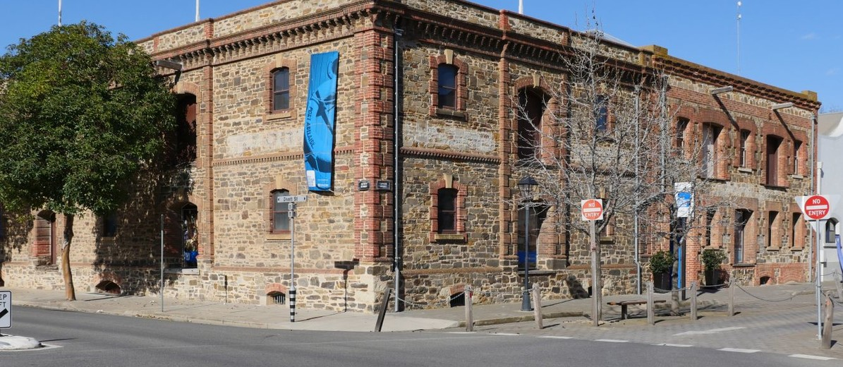 Image: Large stone building on corner with blue banner on closest wall.