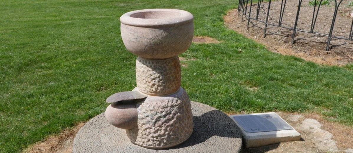 Marble drinking fountain with lawn in the background