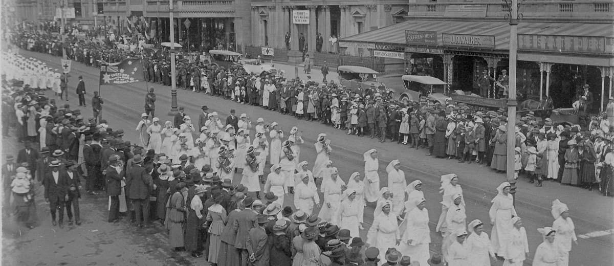 Crowds line street as girls march past, dressed in white with their instruments.