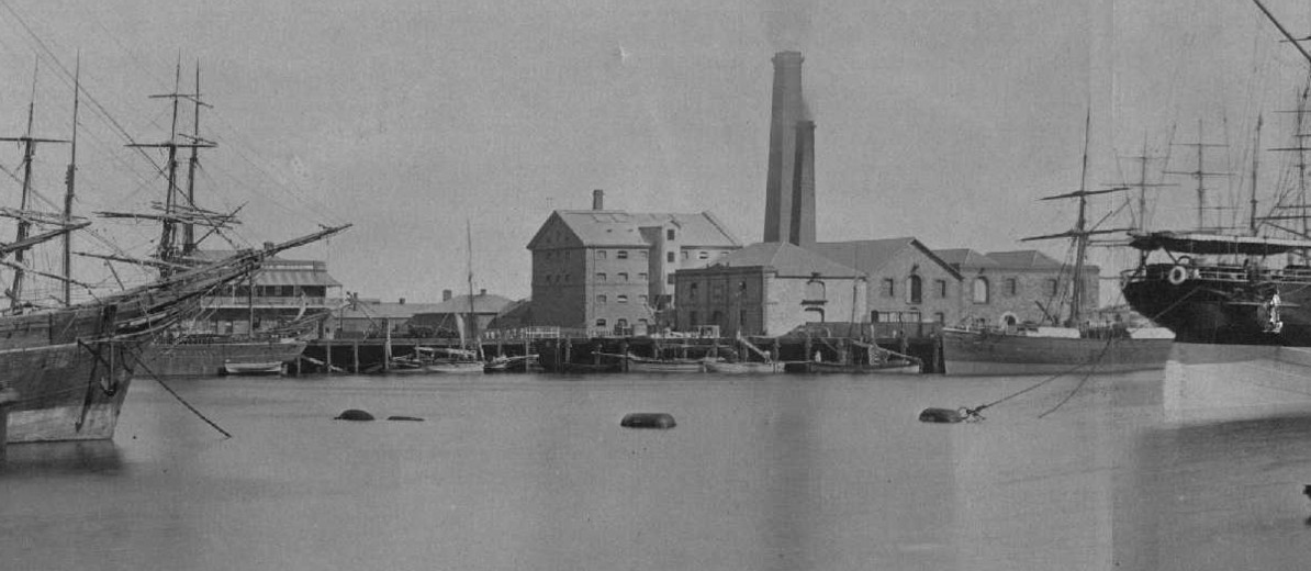 Image: A four-storey stone building is located adjacent to a waterfront wharf. Several ships are visible in the river in the foreground, and two large brick chimneys emerge from behind the stone building