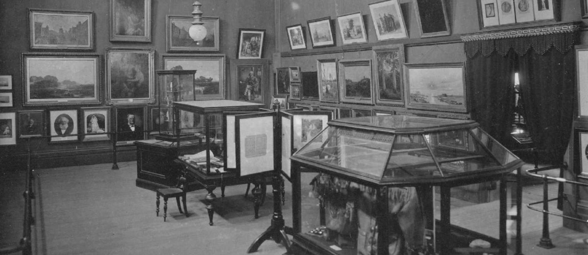 Image: A high-ceilinged room containing several pieces of artwork on its walls and a handful of display cases containing miscellaneous objects