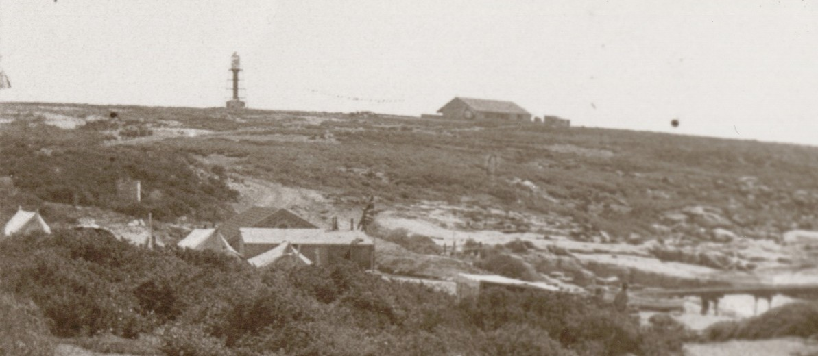 Image: A lighthouse stands at the top of a hill on a desolate island. A low stone building is present next to the lighthouse, and a wooden jetty along the shoreline protrudes into the ocean