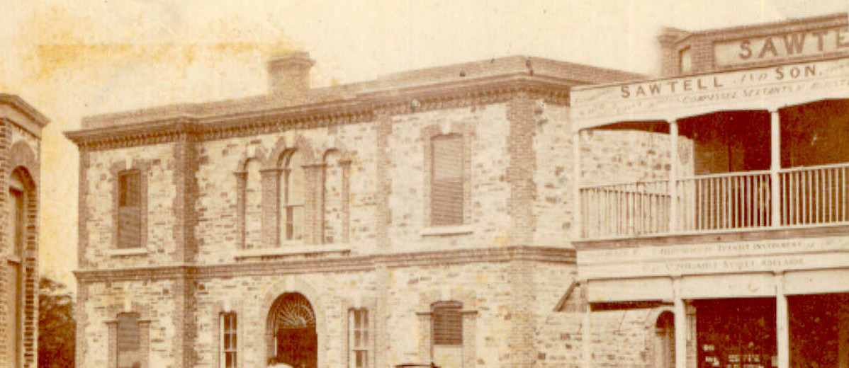 Image: A horse-drawn cart parked in front of three bluestone buildings.
