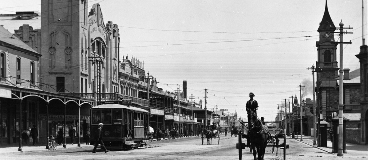 Busy street with several horse drawn carts and one electric tram car, a large building dominates the streetscape