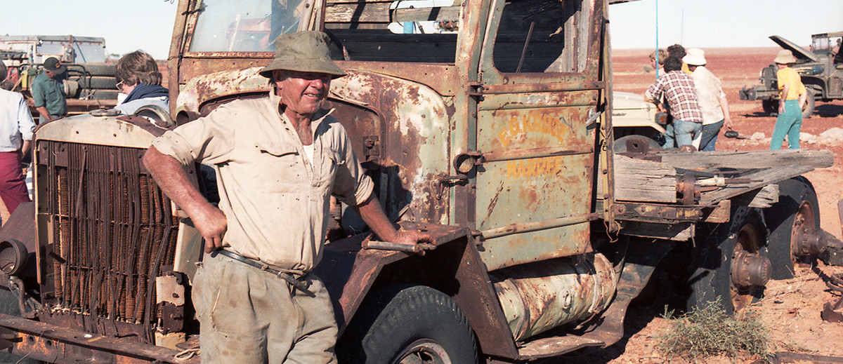 Image: Man leans on rusted truck