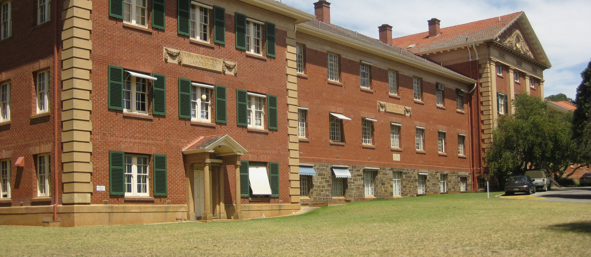 Image: A vey large, three-storey historic brick building with a neo-Classical entry. Two signs with the words 'Ranson Mortlock Laboratory' and 'John Darling Laboratory' are visible on the side of the building