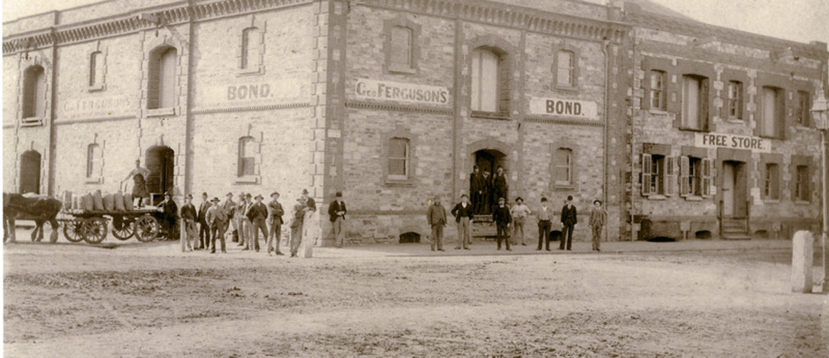 Image: group of men standing in front of large stone building