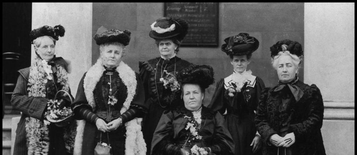 Image: photo of six women wearing black hats and dresses