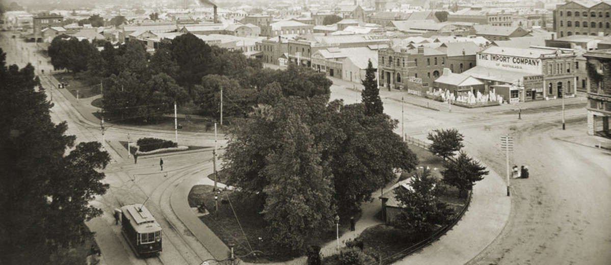 View of a tram and trees in the foreground with cityscape behind