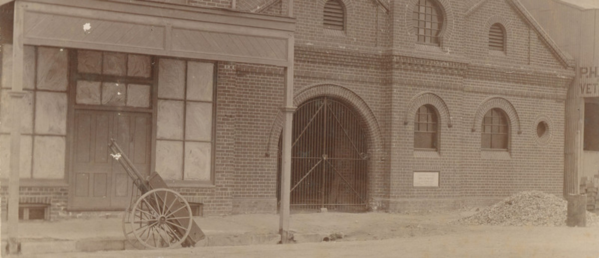 Image: sepia photo of large brick building with arched entrance
