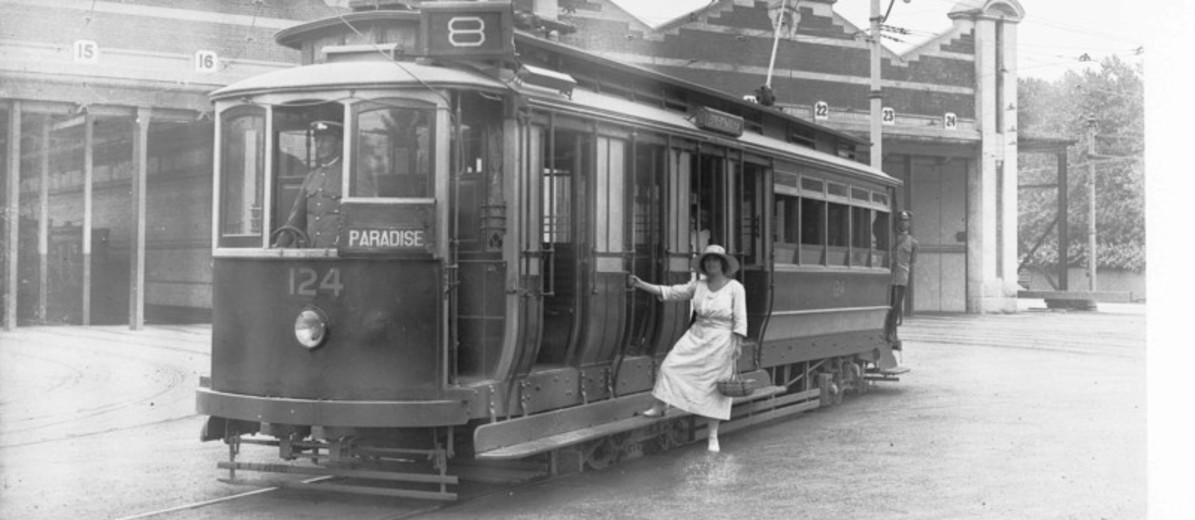 Image: woman standing on step of electric tram